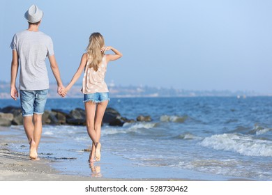 Happy couple walking back on seashore