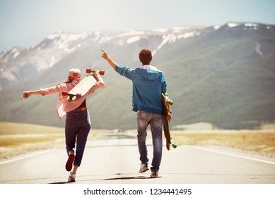 Happy couple is walking by straight road with skateboards or longboards on background of mountains