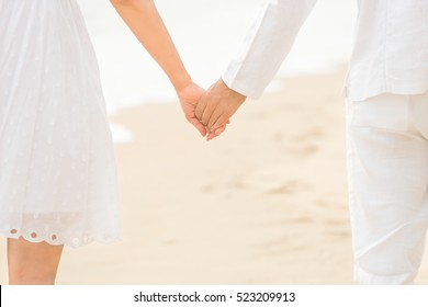 Happy couple walking hand in hand on white sand beach at sunset. Closeup of hand in hand at romantic beach. Will you marry me,love concept.