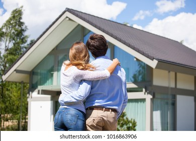 Happy couple walking looking at their house