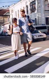 Happy couple walking on crosswalk at sunset in city
