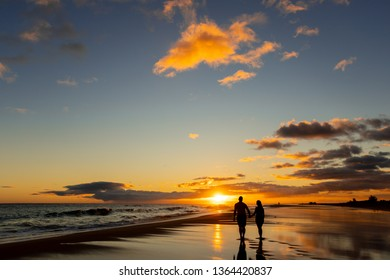 happy couple walking on seashore on a beach vacation or honeymoon trip