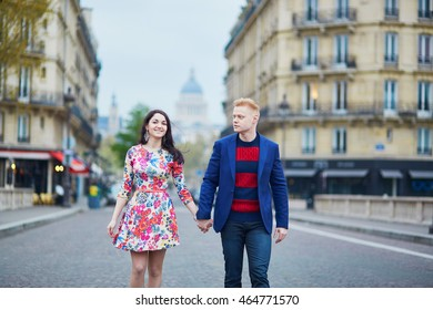 Happy couple walking in Paris. Tourists enjoying their vacation in France. Romantic date or traveling couple concept
