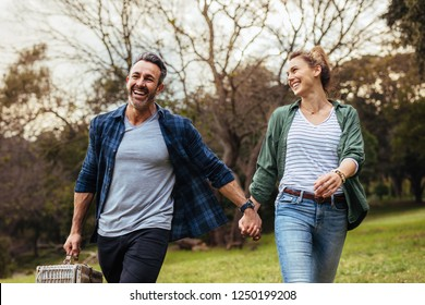 Happy couple walking in the park holding hand and carrying picnic basket. Loving couple going on a picnic at the park.