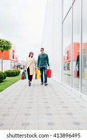 Happy couple walking with shopping bags in shopping center