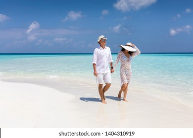 Happy couple walks down a tropical beach with turquoise sea and sunshine