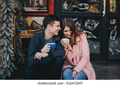 Happy couple in warm clothes drinking coffee on a Christmas market. Holiday mood