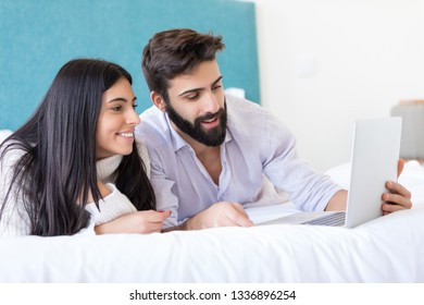 Happy couple watching a movie in bed