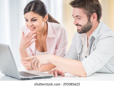 Happy couple watching movie on laptop, sitting at the table at home.