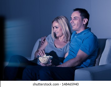 Happy Couple Watching Television And Eating Popcorn At Home
