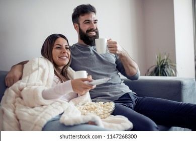 Happy couple watching television,drink coffee and eat popcorn on the couch - family,love,leisure and lifestyle concept.