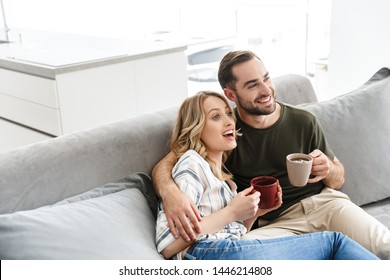 Happy couple watching TV while sitting on a couch at the living room, drinking tea