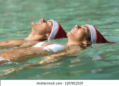 Happy couple wearing santa hats floating in a tropical beach on christmas holiday