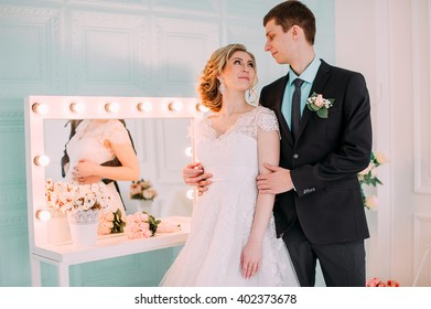 Happy couple. Wedding photo shoot in the white studio with wedding decor kisses, hugs. On the background of make up mirror