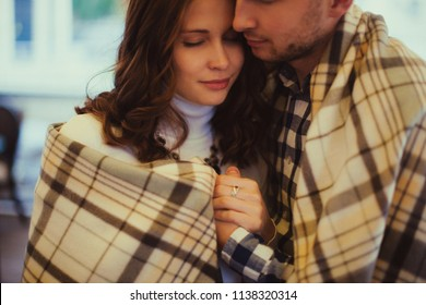 Happy couple of wife and her husband shelter in plaid in the fall. Close up holding hands. Cozy and romantic love concept