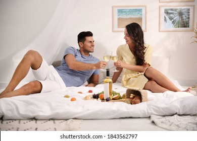 Happy couple with wine and tasty food imitating picnic at home - Shutterstock ID 1843562797