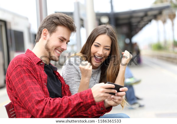 Happy couple winning online games together waiting in a train station
