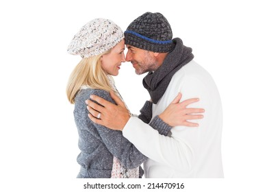 Happy couple in winter fashion embracing on white background