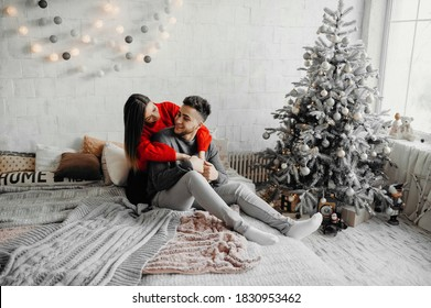 Happy couple in winter sweaters having fun lying on cozy bed and laughing, woman hugging her boyfriend spending winter holidays at home in warm christmas atmosphere