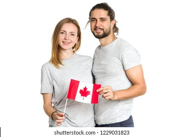 Happy couple of young people with the flag of Canada on a light background. Portraits male and female Canadians, patriots.