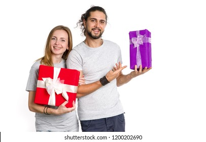Happy couple of young people with gifts in their hands on a light background. Man and woman in a festive mood - New Year, Christmas, Valentine Day.