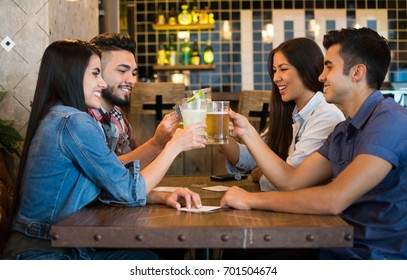 Happy couples at a bar celebrating making a toast with their drinks having fun smiling