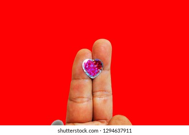 Happy couples concept - Stick the heart shape on these two fingers together on a red background.