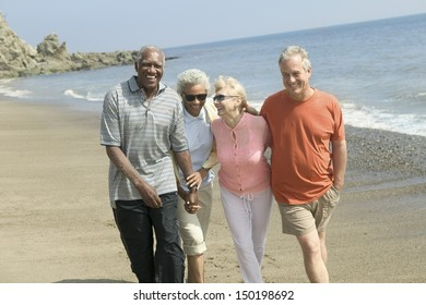 Happy couples walking together on beach