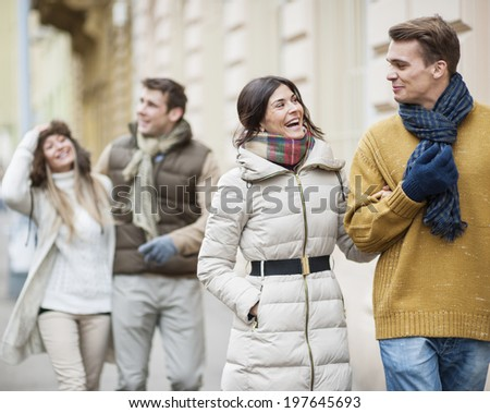 Happy couples in warm clothing enjoying vacation