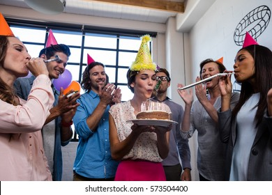 Happy coworker blowing candles for birthday in the office