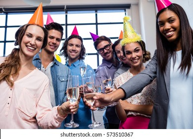 Happy coworker drinking champagne to celebrate a birthday in the office