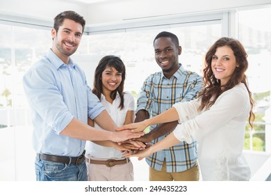 Happy coworkers joining hands in a circle in the office