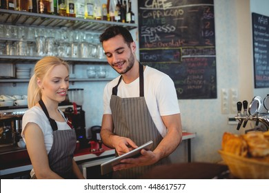 Happy co-workers using digital tablet while standing in cafe
