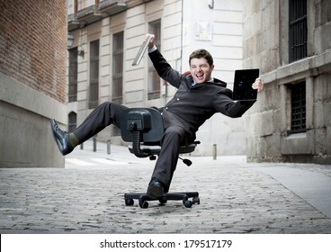 Happy crazy business man rolling downhill on chair with computer and tablet