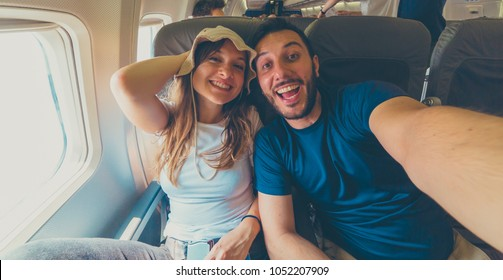 happy crazy cool couple friends in the airplane cabin