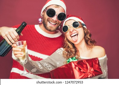 Happy crazy couple drinking champagne celebrating christmas - Millennial young people having fun cheering during xmas holidays - Concept of love, relationship and youth lifestyle vacation