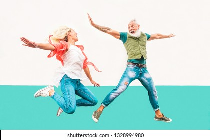 Happy crazy couple jumping together outdoor - Mature trendy people having fun celebrating and dancing outside - Concept of happiness, freedom, carefree, love and relationship