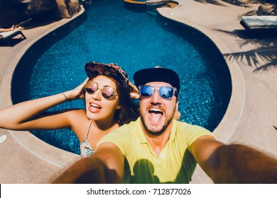 happy crazy couple make selfie near swimming pool, outdoor hipster portrait, fashion model, sunglasses, cap, travel man and female, beard man, smile