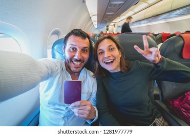 happy crazy couple take selfie on the airplane during flight before landing.They are a man and a woman, smiling and showing passport. Traveling around the world