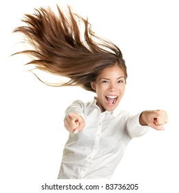 happy crazy excited woman screaming and pointing at camera with wild long hair in the wind. Beautiful ecstatic mixed race Caucasian Asian female model.