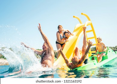 Happy crazy family hands up on floating Playground slide Catamaran as they enjoying sea trip as they have summer season vacation