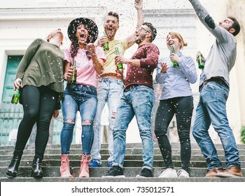 Happy crazy friends celebrating on the street drinking beer and throwing confetti - Young students having fun together - Friendship and youth concept - Vsco warm filter - Main focus on center guys