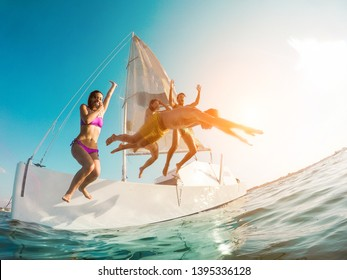 Happy crazy friends diving from sailing boat into the sea - Young people jumping inside ocean in summer vacation - Main focus on left girl body - Travel and fun concept - Fisheye lens distortion