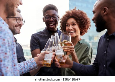 Happy creative business colleagues having a drink after work raise glasses to make a toast