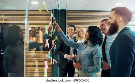 Happy creative businesspeople brainstorming in office, placing sticky notes with ideas on glass