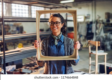 Happy creative middle age female carpenter holding picture frame in front of her face. Standing in her workshop.