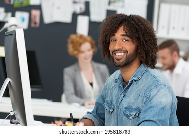 Happy creative modern African American businessman in a casual denim shirt sitting in a multiethnic office at his desktop computer smiling at the camera