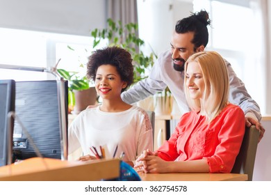 happy creative team with computer in office