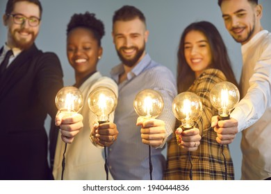 Happy creative team holding glowing lit lightbulbs. Diverse collaboration group of intelligent young multicultural business people with shining light bulbs presenting and sharing effective useful idea