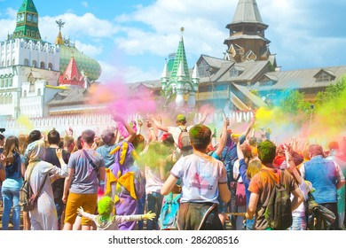 Happy crowd of young people on beautiful square celebrate Indian holi festival with colorful paint powder on faces and body